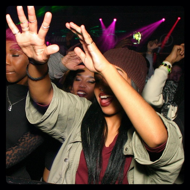 A Black girl has hands in the air at a concert in a Downtown Orlando nightclub.