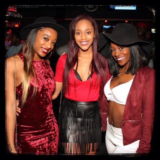 Three smiling black women in an Orlando nightclub.