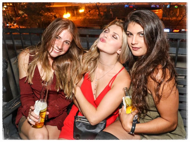 Three young ladies sitting on a bench in a Downtown Orlando rooftop bar.