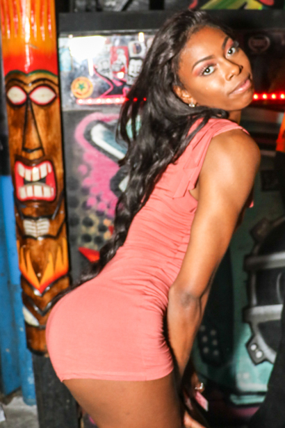 Young black woman giving a booty pose in Downtown Orlando nightspot.