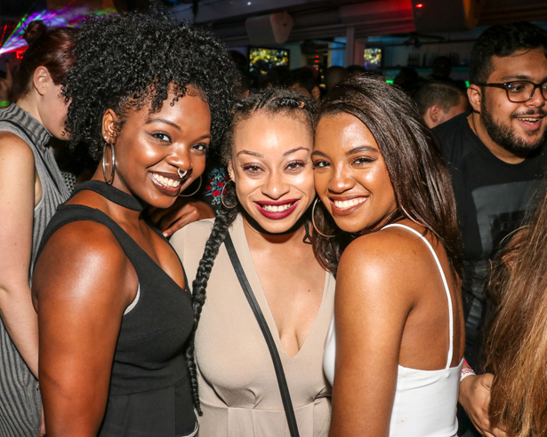 Three black women smiling at a rooftop bar in Downtown Orlando.