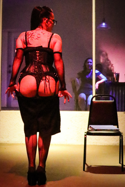 A Brunette burlesque dancer is pulling down her skirt with her booty towards the audience.