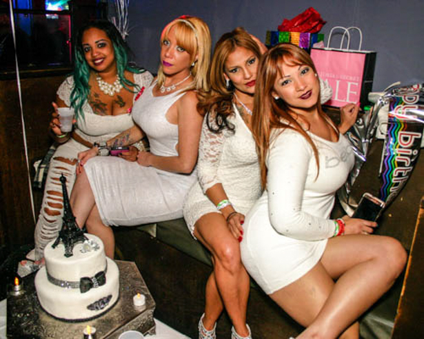 Four Hispanic women dressed in white sitting in a nightclub's VIP section.