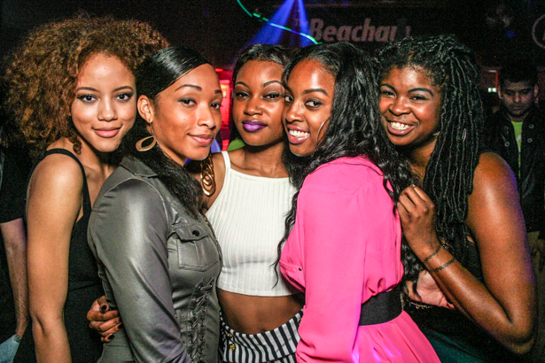 Five young black women smiling in a nightclub.