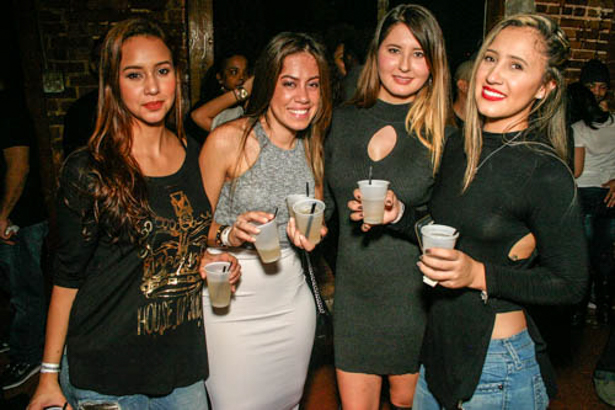 Four young Hispanic women smiling and holding drinks.