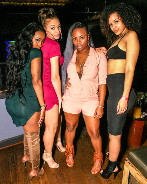 A full-bodied photo containing four women of color.