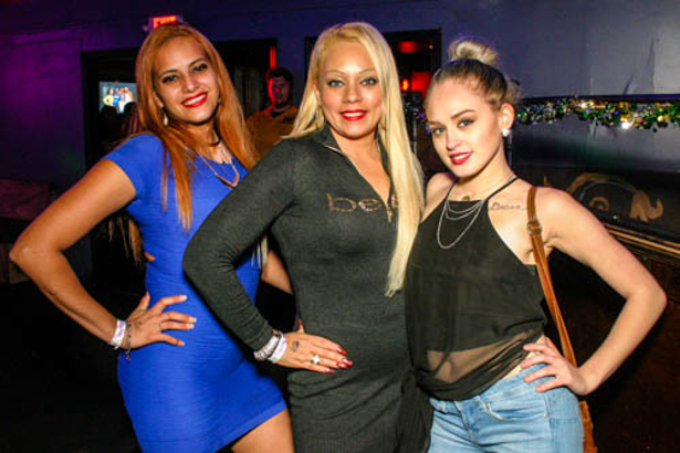 Three Hispanic women with hands on their hips.