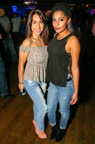 Two Hispanic women posing in a nightclub.