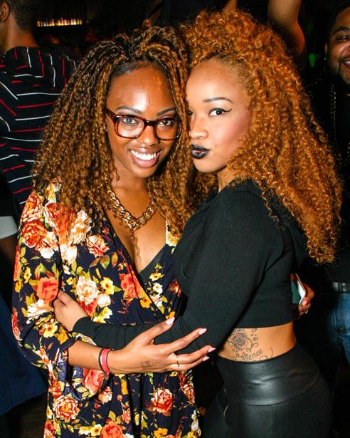 Two black girls hugging in a nightclub.